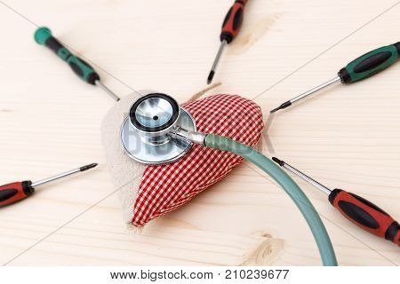 Fabric red heart stethoscope and srewdrivers around on wooden table - health condition and healthcare concept
