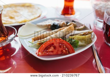 Close-up: plate with vegetarian food - bread roll with fresh vegetables cheese and olives next to glass with drink on red cafe table