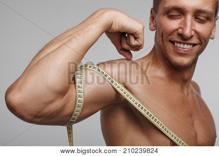 Young happy sportsman posing shirtless and measuring bicep with tape on gray background.