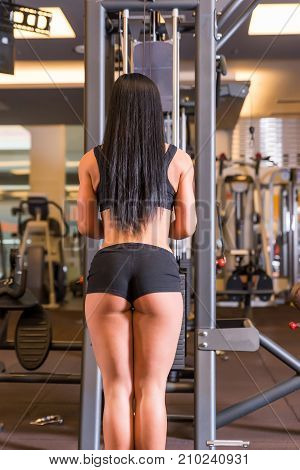 A beautiful young woman working on a weight lifting machine in the Gym.