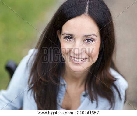 a headshot of a pretty brunette looking up at the camera