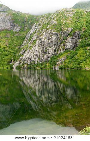Rocky coast in the fog on the lake Hamnoyvatnet Lofoten Norway. National Tourist Route Lofoten