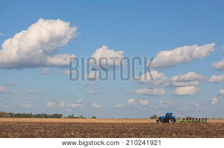 A Large Blue Tractor, Plowing Field Against The Beautiful Sky. Work Of Agricultural Machinery. Harve