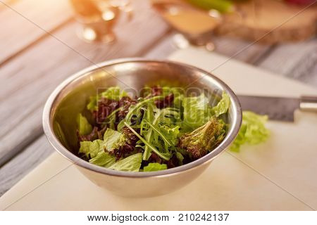 Mixed salad leaves in stainless bowl. Fresh mix of green and purple salad on table. Dish cooking at restaurant.