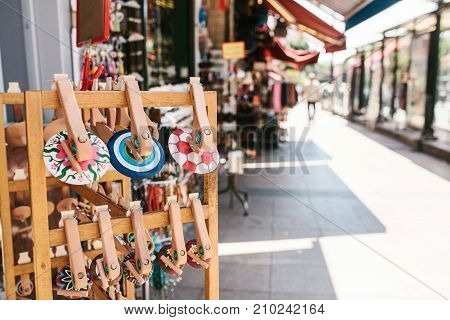 Close-up - painted Turkish wooden souvenirs on the street against the background of blurry street stalls and shops