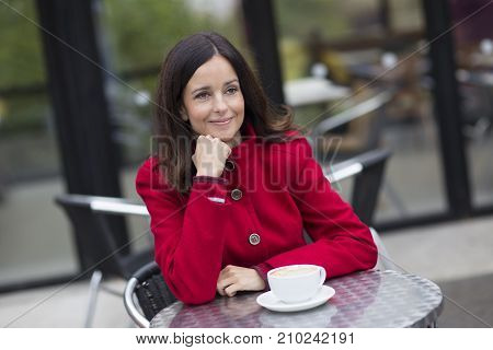 Thoughtful girl having a cup of coffee