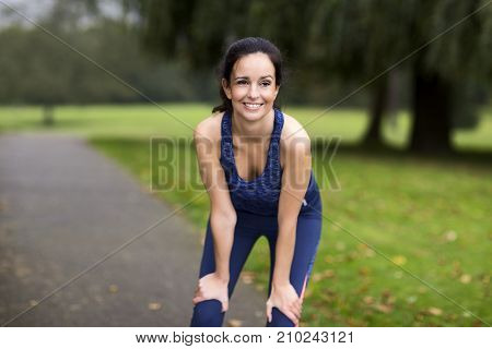 young woman catching her breath after a run in the park