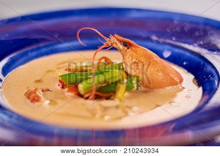 Cream soup with crayfish tails and vegetables. Tasty soup puree with vegetables and crayfish. Delicious dinner on plate close up.