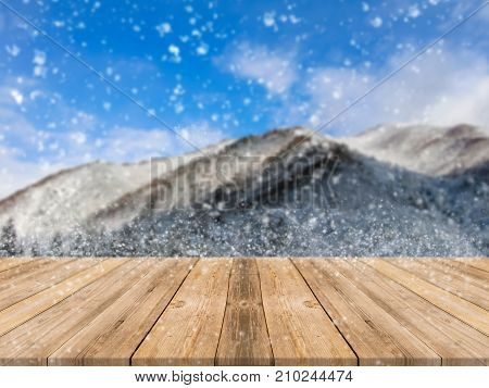 Wooden board empty table top on of blurred snowfall background. Perspective brown wood table over blur winter blue landscape background