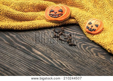 Halloween holiday background with cookies clove and wool clothes