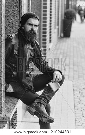 bearded man long beard brutal caucasian hipster with moustache holding metallic flask jar has serious face in black leather jacket hat scarf unshaven guy with stylish hair at building outdoor