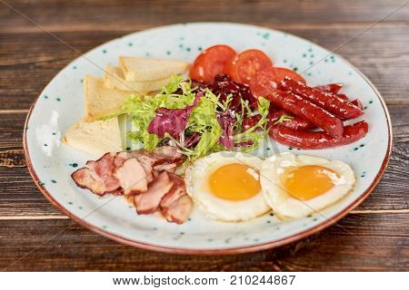 English breakfast with fresh salad. English breakfast - fried eggs, baked bacon and sausages, toasts, tomatoes and green salad. Appetizing dish on plate.