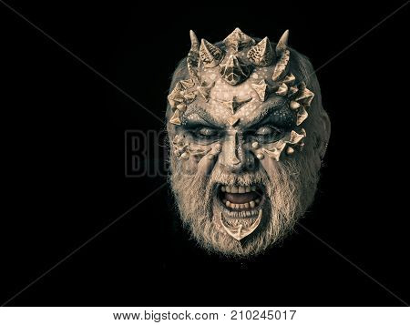 Evil face with dragon skin and grey beard. Man angry with blind eyes. Monster with thorns and horns. Demon baring teeth isolated on black. Horror and fantasy concept.