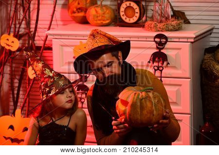 Girl and bearded man with interested faces on red spooky carnival room background. Dad and daughter with Halloween decor. Halloween party concept. Wizard and little witch in witch hats carve pumpkin