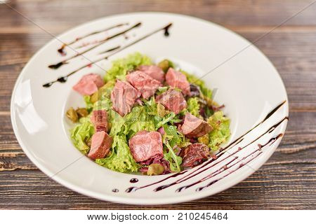 Green salad with beef, cornichons and mustard. Appetizing and healthy salad in restaurant. Delicious dinner on plate.