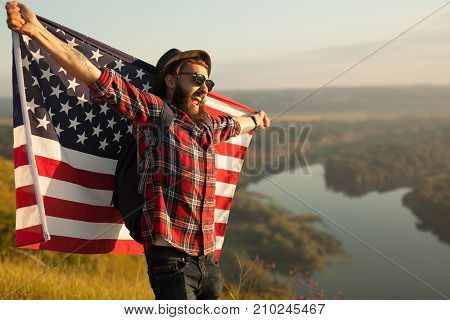 Young hipster man with backpack posing happily holding American flag on background of nature.