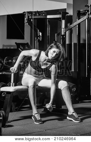 pretty woman or cute girl with sexy body in yellow pants training in sport gym with metallic dumbbells relax near trainer