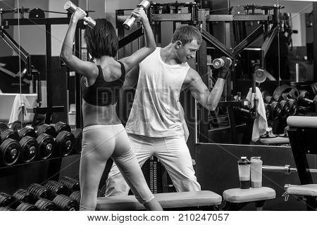 happy smiling couple of pretty woman or cute girl with sexy buttocks and handsome man with muscular body training in sport gym at black trainer with metallic dumbbells