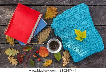 Fallen autumn leaves on the old wooden background hot cup of coffee book and warm knitted sweater. Cozy interior. Morning in the forest. Reading education and inspiration. Beautiful autumn time.