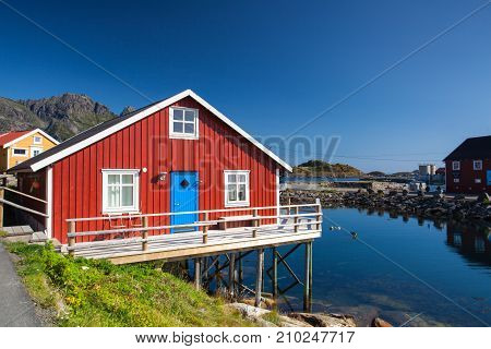 Henningsvaer Norway - August 192017: Picturesque fishing port in Henningsvaer on Lofoten islands Norway with typical red wooden buildings and small fishing boats