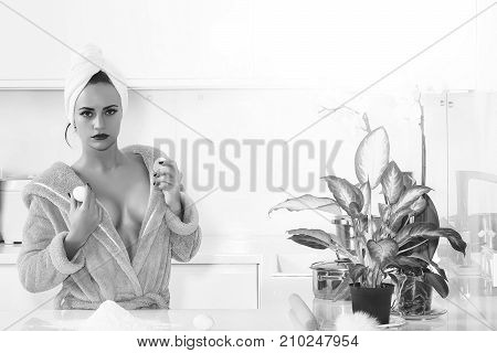 One sexual beautiful sensual female housewife in blue terry dressing gown and towel turban on head with bare shoulders standing in kitchen cooking breakfast from eggs in morning life horizontal