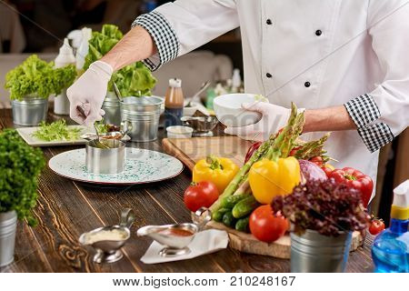 The process of cooking food at kitchen. Chef preparing food from fresh vegetables. Cook at work, restaurant.