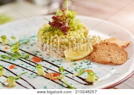 Delicious salad with toasts and lemon. Salad with herring in belgian style, avocado and toasts. Tasty dish on plate.