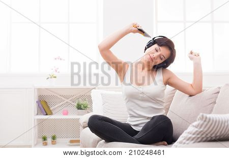 Move your body. Excited girl listening to music in earphones, holding her phone. Girl wearing casual clothes, sitting on cozy beige couch, with her eyes closed and hands up. Technology and enjoyment