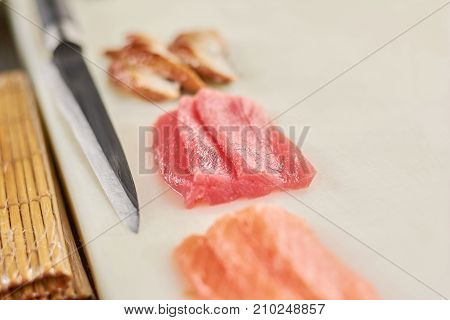 Fillet of raw tuna, salmon and eel. Ingredients for cooking nigiri sushi on white cutting board. Raw fish pieces and knife close up.