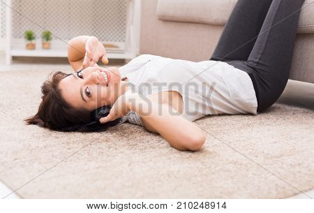 Young brunette woman with a tender smile enjoying the music in headphones and relaxing while lying at home on floor carpet, with her legs up on the sofa. Technology and enjoyment concept.
