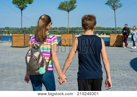 Couple teens holding hands rear view. Friendship first love.