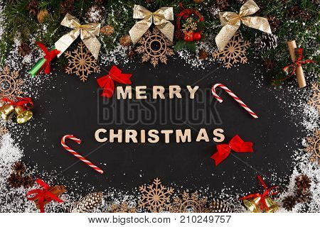 Merry christmas greeting, decoration background, top view on pine tree twigs with pine cones, nuts, golden bows, bells and snowflakes frame with wooden letters and lollipops