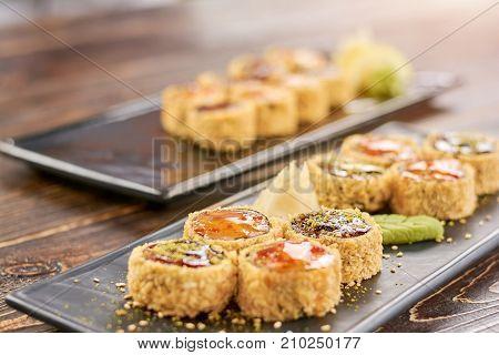 Sushi roll set at sushi bar. Delicious japanese sushi set. Appetizing unagi sushi rolls on traditional japanese dish.