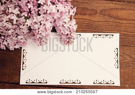 wooden table bouquet flowers of pink lilac attached greeting cards