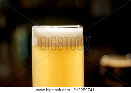 Cold lager beer on counter. Glass of fresh beverage with foam on dark bar background. Cropped image of glass with light beer.
