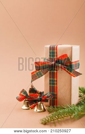 Creative christmas gift boxes in craft paper, xmas bells and pine branches on beige background with copy space. Christmas, birthday or valentine day present concept