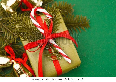 Creative xmas gift box decorated with red ribbon, candy cane lollipop, pine tree twigs and gold xmas bells on green background, copy space. Winter holidays presents and christmas decorations concept