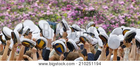 STOCKHOLM SWEDEN - JUN 13 2017: Hands holding many swedish white graduation caps lilac flowers in the background at the dance school Balettakademien June 13 2017StockholmSweden