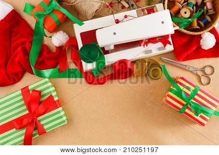 DIY christmas hobby background. Sewing machine, gift box, ribbons, basket with threads and santa hat on table, top view. Handmade craft new year gifts, creative leisure, copy space