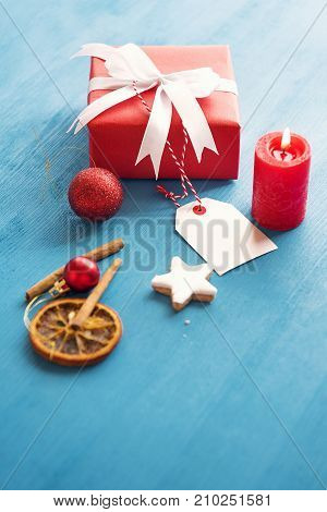 Vertical image of an elegant gift wrapped with red paper and tied with white ribbon and bow with an etiquette attached to it in a Christmassy decor.