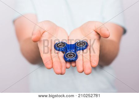 young man playing with a fidget spinner, focus on spinner