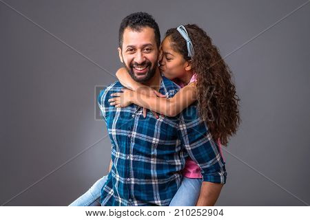 A young black man standing and caring his daughter on his back while she giving him a kiss on his neck
