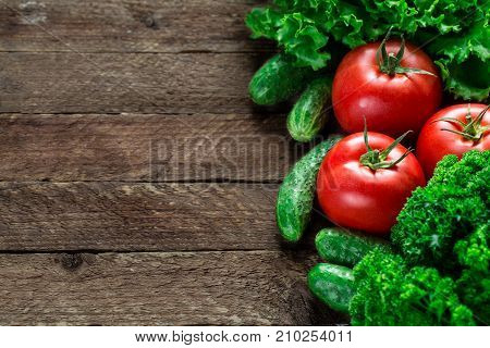 Fresh tomatoes, cucumbers, salad on wooden background