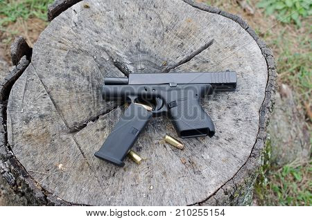 Semi-automatic weapon with clip and bullets displayed. Personal protection and safety against violence and crime. Sport activity of target shooting.
