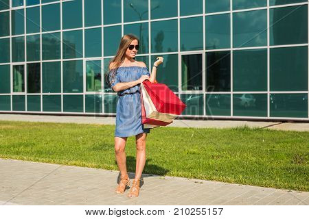 Sale, shopping and happy people concept - beautiful woman with shopping bags walking on a street.