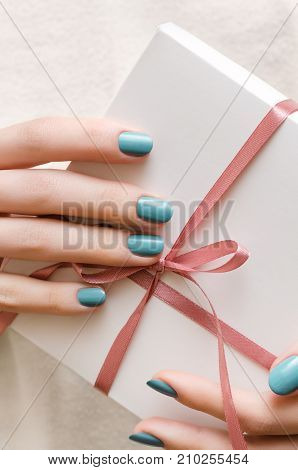 Female hands with turquoise manicure holding white gift box.