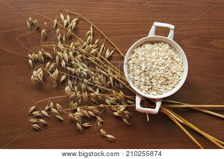 Oat Ears Stems And Oat Flakes In A White Pot On A Dark Brown Wood Background. Top View. Oat Flakes S