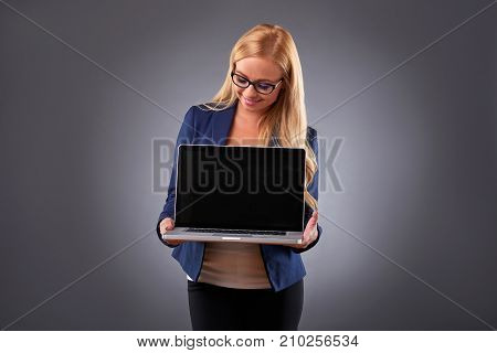 A beautiful young woman in eyeglasses showing and looking at the screen of the laptop in her hands
