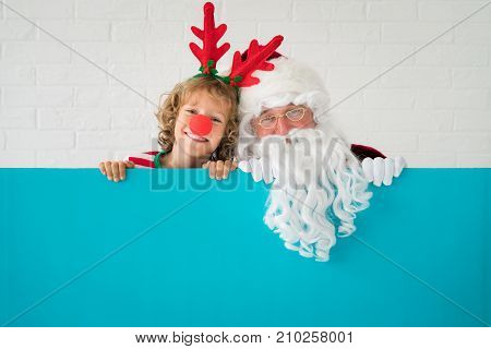 Santa Claus and reindeer child holding banner blank. Merry Christmas greeting card. Xmas holiday concept