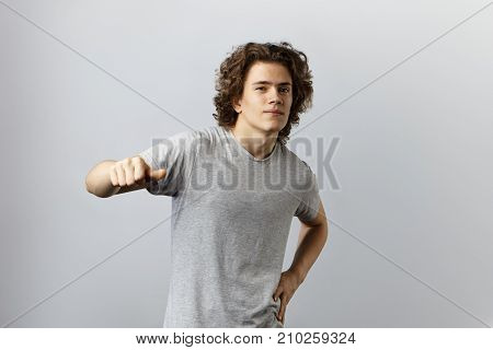 Picture of confident bigheaded young Caucasian man with curly hairstyle looking at camera with arrogant smile showing thumbs up gesture and pointing at himself. Confident self love and inflated ego
